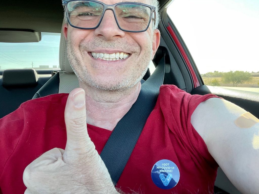 "Selfie with a thumbs up signal, a Band-Aid on my shoulder, and a sticker that says ""I got my COVID-19 vaccine!"""